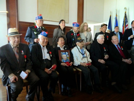 Eight World War II veterans and representatives of two posthumous honorees pose for a group photo with Consul General Pauline Carmona.