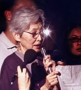 Lillian Nakano reading NCRR's statement in support of the Muslim community at a candlelight vigil shortly after 9/11, when Muslims and those perceived as Muslims were targets of hate crimes, including murder.