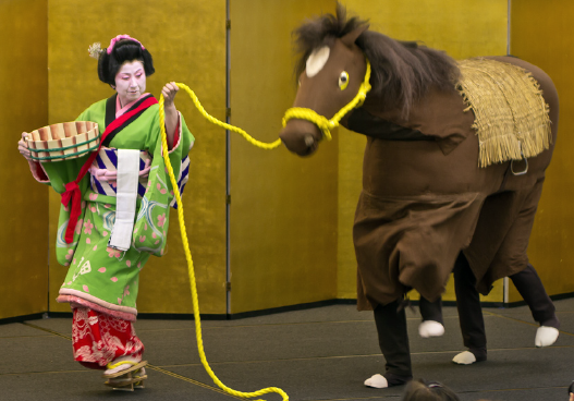 Okane is a sarashime (cloth bleaching girl) who lives on the shores of Lake Biwa, Japan. Famed for her strength, Okane is shown stopping a runaway horse with one hand while holding a bucket with the other. The horse is performed by Fujima Kansusumi (Dr. Sumi Kawaratani) and Peter Lai.