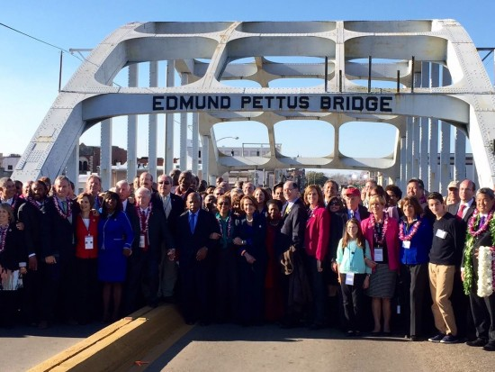 "Members of Congress gather at the Pettus Bridge in Selma, Ala., the site of ""Bloody Sunday"" 50 years ago. (Office of Rep. Mark Takano)"
