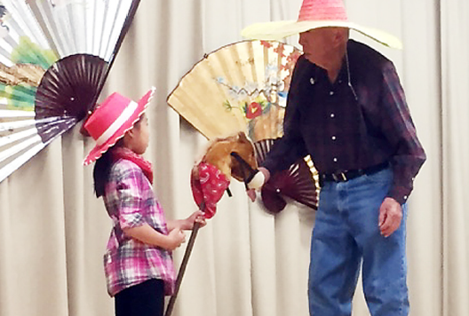 Ken Kageyama, Valley Japanese Community Center president, performs a magic trick with his grandchildren.