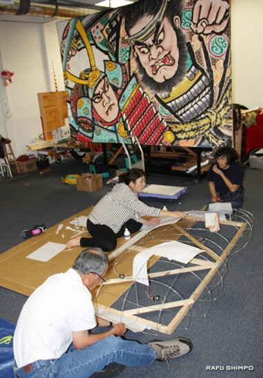 Above and below: Volunteers cover the wire frame of the float with paper.