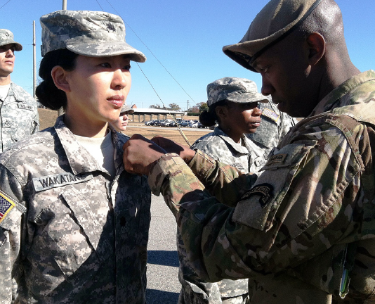After completing five parachute jumps, Lt. Col. Kay Wakatake had her wings pinned on by Sgt. First Class Raymond Richardson, senior paralegal NCO, 75th Ranger Regiment, Fort Benning, Ga. (Photo by Capt. Greg Peterson, 75th Ranger Regiment, Fort Benning, Ga.)