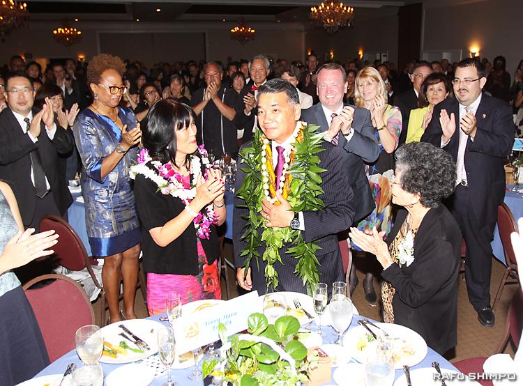 参加者500人からスタンディング オベーションを送られ感涙にむせぶハラ氏(中央)