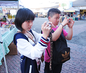 ダウンタウンのアートディスクリクトで開かれたファーマーズマーケットに行き、カメラを構える福留さん(左)と宝満さん
