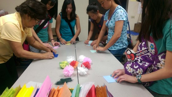 Junko Yonezawa (left), chair of the workshop committee for the Los Angeles Tanabata Festival, demonstrates how to make flowers for kazari Japanese decorations for the upcoming Los Angeles Tanabata Festival, to be held Aug. 14 to 17 in Little Tokyo.