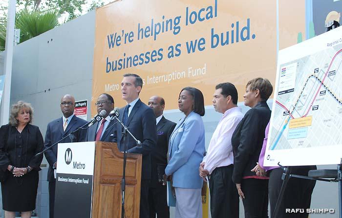 6日、ミラクルマイルで開かれた記者会見で、鉄道工事の影響を受けている小企業支援の大切さを訴えるロサンゼルスのエリック・ガーセッティー市長(中央)と関係者ら