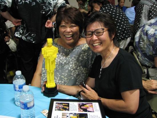 Cousins Vickie Tani and Lisa Joe with one of the auction items, a Lego Oscar created by Oscar winner Chris Tashima.