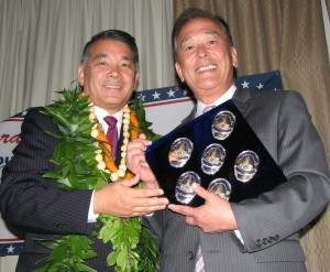 "Terry Hara receives a ""blue diamond"" containing his LAPD badges from Gerald Fukui."
