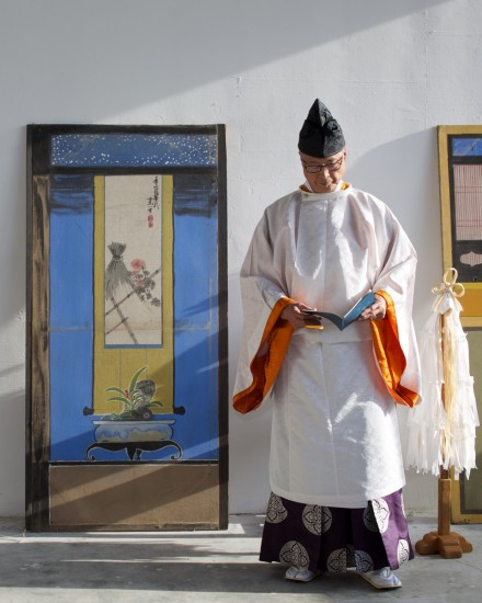 Rev. Masato Kawahatsu of Konko Church of San Francisco blessed the exhibit at the gallery opening. He is standing in front of pre-war kabuki backdrops found in the Buddhist Church of San Francisco's basement.