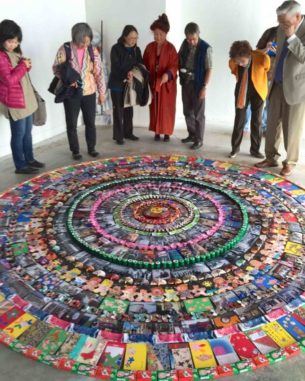 Brenda Wong Aoki, in red kimono, explains the elements of artist Nancy Hom's Japantown Mandala, composed of hundreds of historical references to the history of San Francisco's Japantown, one of three Japantowns remaining in the U.S.
