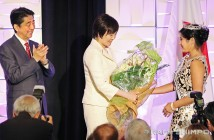 Nisei Week Queen Tori Nishinaka-Leon presents a bouquet of flowers to Japanese First Lady Akie Abe as Prime Minister Shinzo Abe applauds on Friday at the Millennium Biltmore Hotel. (JUN NAGATA/Rafu Shimpo)