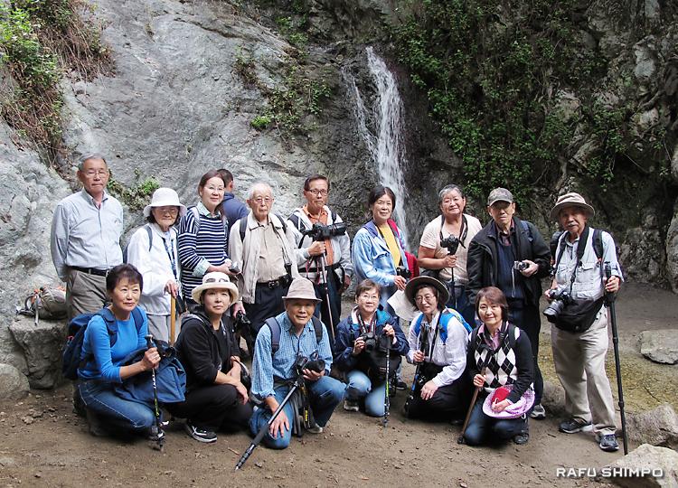 滝をバックに集合写真に収まる参加者。後列の右端が講師の岡田信行さん、左端が講師助手の緒方義親さん