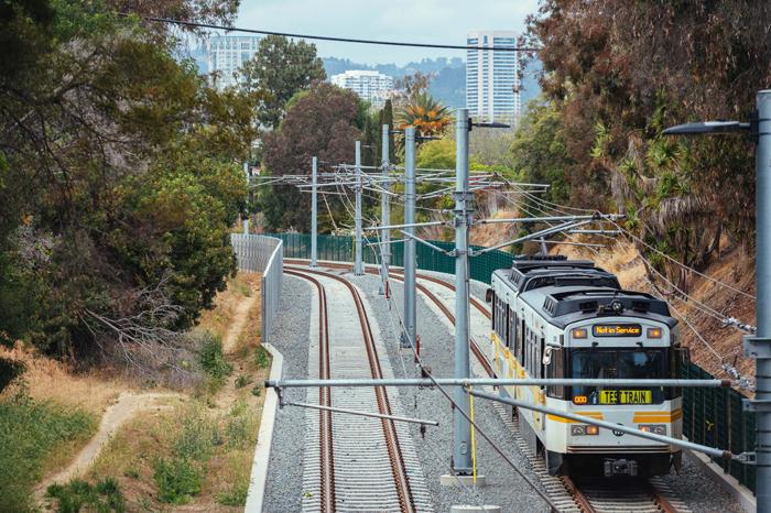 ウエストウッドを背景に、オーバーランド通りに向け試運転するエクスポライン(写真=メトロ提供)