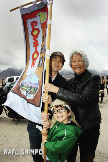 Hatsuko Mary Higuchi, her son Mark and her grandson hoist the Poston banner. All 10 WRA camps were represented.
