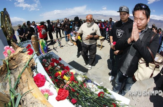 Manzanar Pilgrimage participants place flowers at the Ireito (Soul-Consoling Tower) in the camp cemetery.