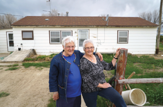 Ruth Blackburn Pfaff and Jane Blackburn Chelberg in front of their former home, a barracks from the Heart Mountain concentration camp. (Photo by Stan Honda)