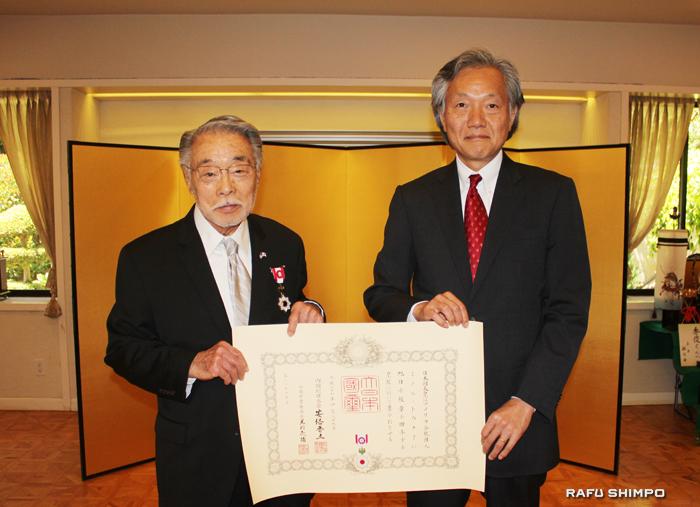 堀之内総領事(右)から勲章と賞状を伝達されたトウナイ氏