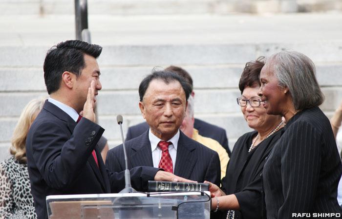 就任宣誓を執り行うバーク氏(右)と両親(中央)が見守る中、初の韓国系市議に就任したリュー氏