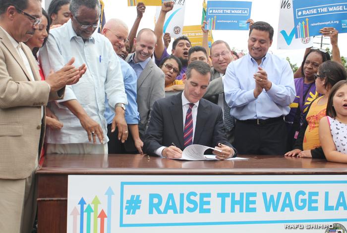 LA市の最低賃金引き上げ案に署名するエリック・ガーセッティー市長(中央)