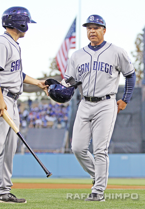 Dave Roberts, then a first base coach for the Padres, help clear equipment after the team's at-bat during a game at Dodger Stadium on April 17, 2013. After San Diego fired Bud Black on Monday, Roberts took over as manager – for one game. (JUN NAGATA/Rafu Shimpo)