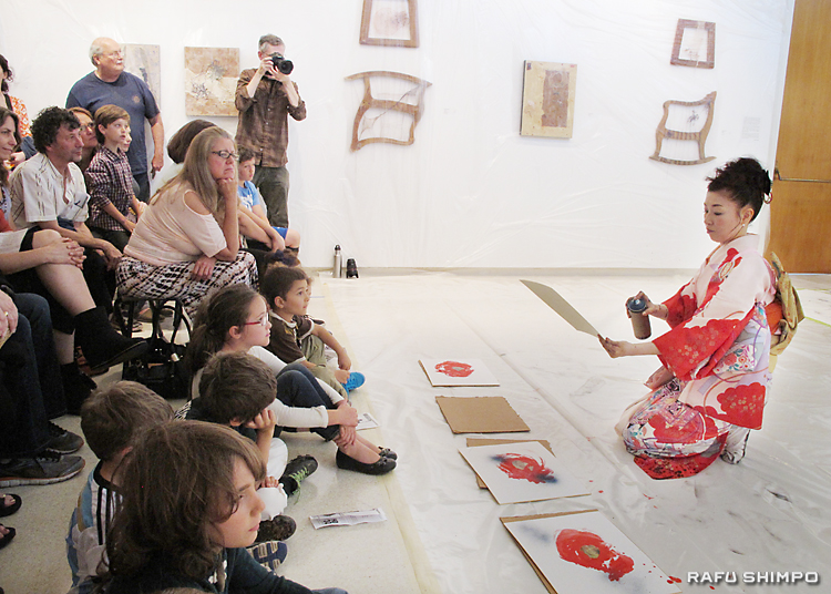 スプレーを使い、色紙に椿の葉を描く平野さん(右)のパフォーマンスを凝視する参加者