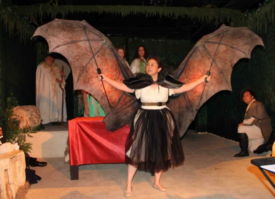 "At Prospero's command, Ariel (Randi Tahara) appears as a harpy to tell the King and his court why they are being punished and what lies in store for them in a scene from the Long Beach Shakespeare Company's production of ""The Tempest."" (Photo by Cindy Rinks)"
