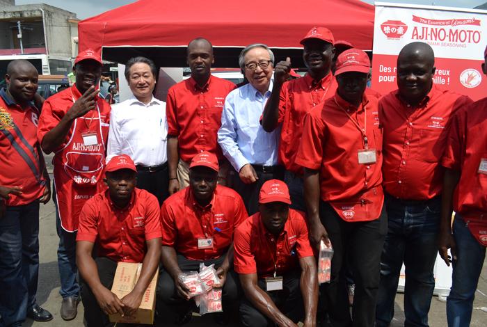 2014年1月に同社ナイジェリア法人を訪問し、市場視察した際の伊藤会長(後列左から5人目)。赤い制服の現地営業マンたちとともに (味の素社提供)