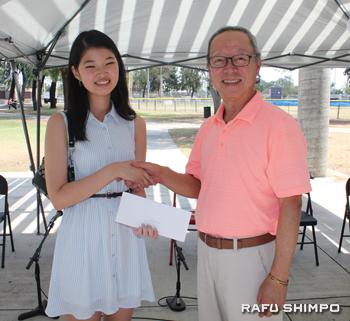 奨学金を手渡す宗会長(右)と今年授与された赤石明美さん