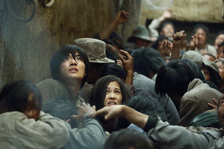巨人の襲撃から逃げる人々。エレン(左、三浦春馬)と、ミカサ(右、水原希子)©FUNimation Entertainment