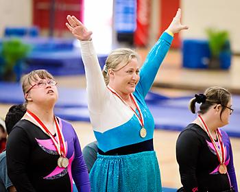 体操競技でメダルを獲得しポーズを決めるアスリートたち©Cory Hansen
