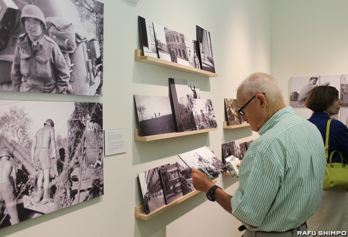 展示されている写真に見入る来場者。写真の一部は手に取ってみることも出来る