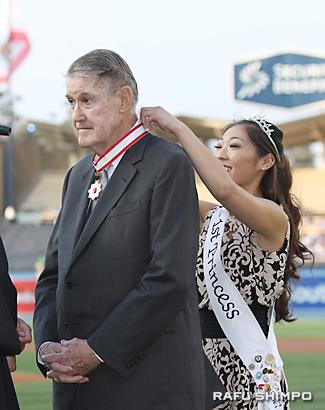 旭日中綬章のメダルを二世週祭ファースト・プリンセスのリンジー・スギモトさん(右)に掛けてもらうオマリー氏