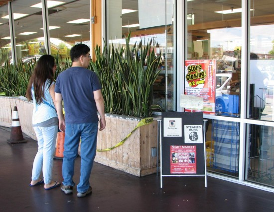Shoppers read the notice posted in front of the store.
