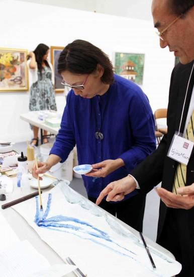 Nihonga-In Senior General Manager Yujiro Miura shows how to apply iwa-enogu to washi. (ICHIRO SHIMIZU/Rafu Shimpo)