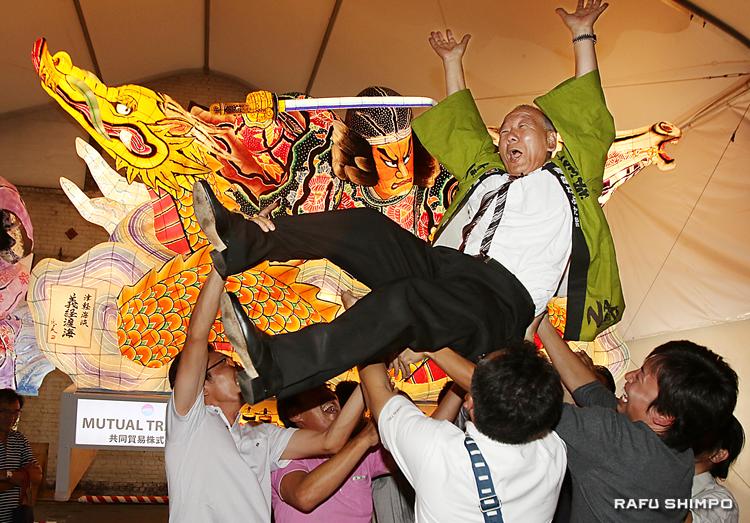 ねぶたを背に囃子保存会のメンバーら有志に胴上げされ、宙を舞う豊島年昭会長