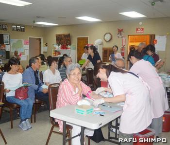 広島大学医師団の検診会場で採血する受診者
