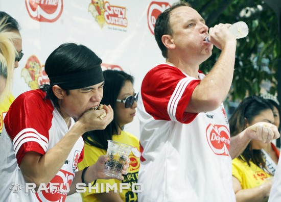 "Matt ""The Megatoad"" Stonie gobbles gobs of gyoza as rival Joey ""Jaws"" Chestnut washes his down, during Saturday's Day-Lee Foods World Gyoza Eating Championship at the JACCC Plaza in Little Tokyo. Stonie ate a scant four more dumplings than Chestnut to win the title. (MARIO G. REYES/Rafu Shimpo)"