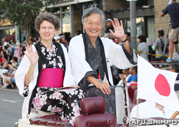 沿道からの声援に手を振り応える堀之内秀久・在ロサンゼルス日本国総領事とサビーン夫人