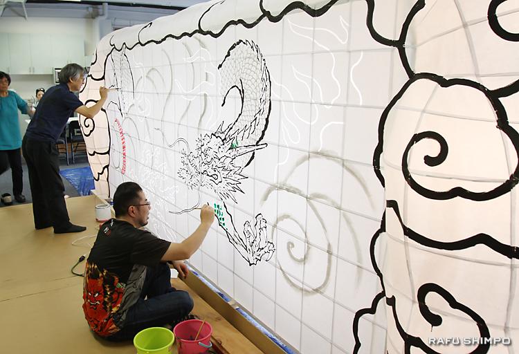 背面の「見送り」の部分の龍の輪郭を描く竹浪比呂央師(左奥)と手塚茂樹さん
