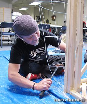 木枠に針金の枠組みを取り付ける作業を行う長尾博さん