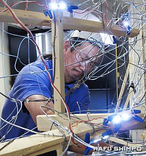 自身3つ目制作のねぶた「那須与一 扇の的」にLED電球をつける作業を行う山村俊夫さん