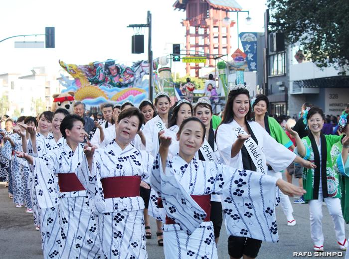 東1街を踊りながら進む坂東秀十美、サラ・クニコ・ハッター二世週祭クイーンら