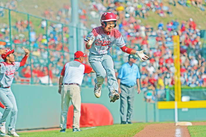 Japan's Kabu Kikuchi leaps in the air at third base after teammate Masafuji Nishijima clubbed a third- inning home run during the Little League World Series championship game, Sunday in South Willamsport, Penn. Japan won the title in a slugfest, outpowering a team from Lewisberry, Penn., 18-11. Photos courtesy of Little League Baseball and Softball