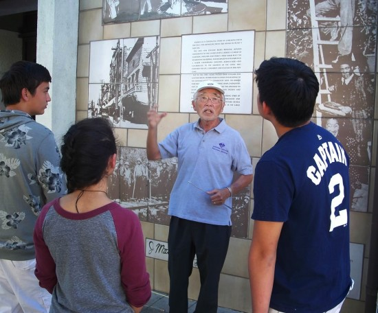 """During a walking tour of Little Tokyo, Bill Shishima describes """"Senzo,"""" a 20-foot photo-on-tile collage."""