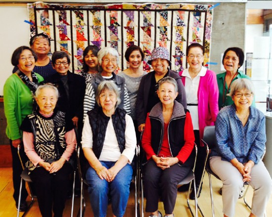 "Quilters pose next to this year's quilt, ""Bamboo II,"" at the Little Tokyo Branch Library."