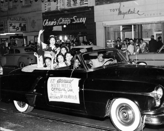 Yoshinaga drives the car as Nisei Week Queen Em Kato waves during the 1952 Nisei Week Grand Parade.