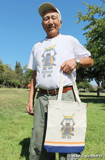 若い人たちを応援する米澤会長。オリジナルTシャツと手提げバッグを身に付けて記念撮影「ハイ、チーズ!」