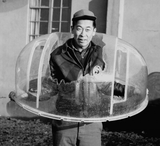 Ben Kuroki holding the shattered Plexiglass turret from his 30th bombing mission over Europe. Had a radio man not tugged on his pant leg, causing him to bend down to see what he wanted, Kuroki would have been killed by the shell that hit the turret. (Photo courtesy of Jean Lukesh)