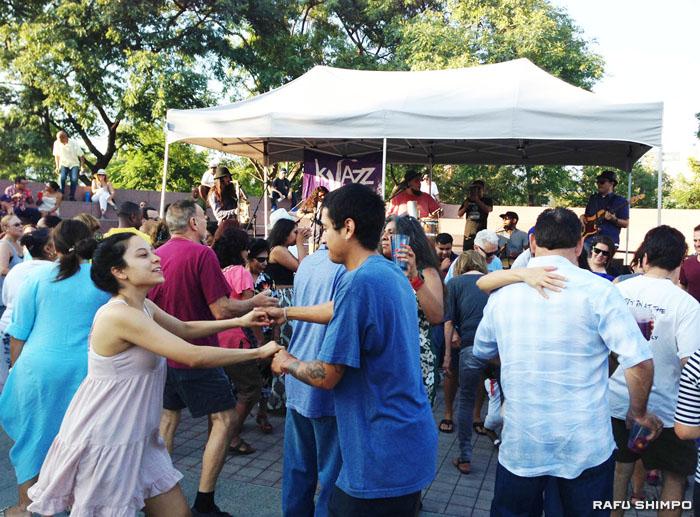 アーティストが演奏するラテンミュージックに合わせて踊る人々